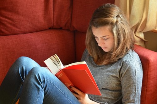 In this image, a student us sitting in a red chair and reading a book.