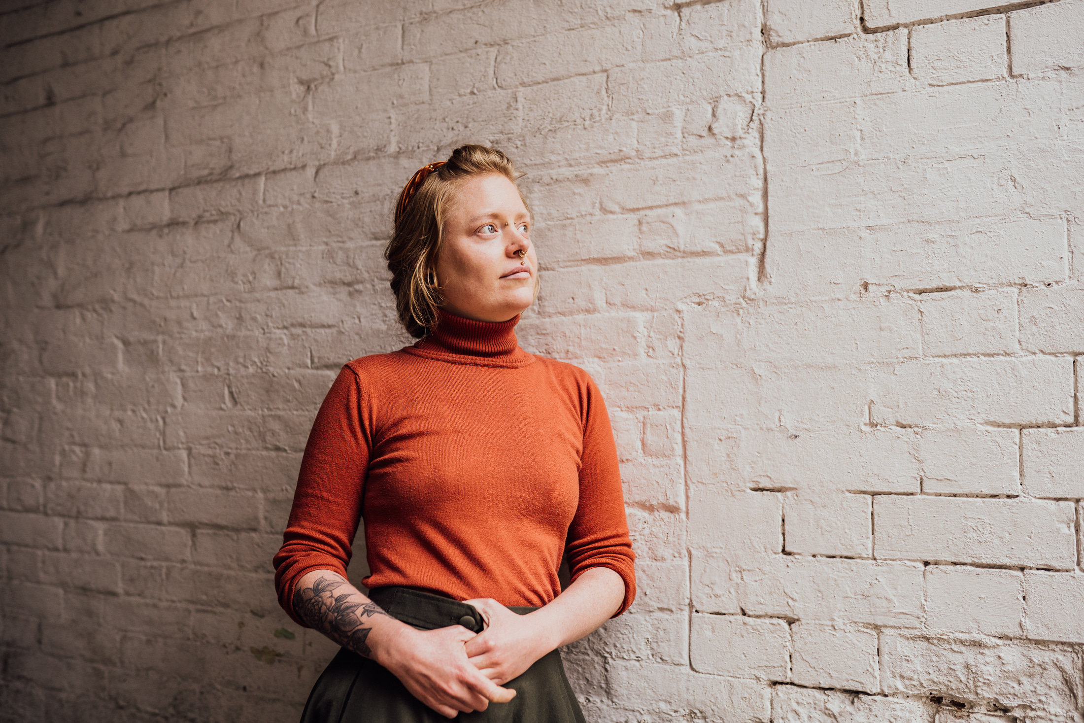 In this image, Jess from Rogue Piercing is leaning against a white, brick wall and wearing an orange top.