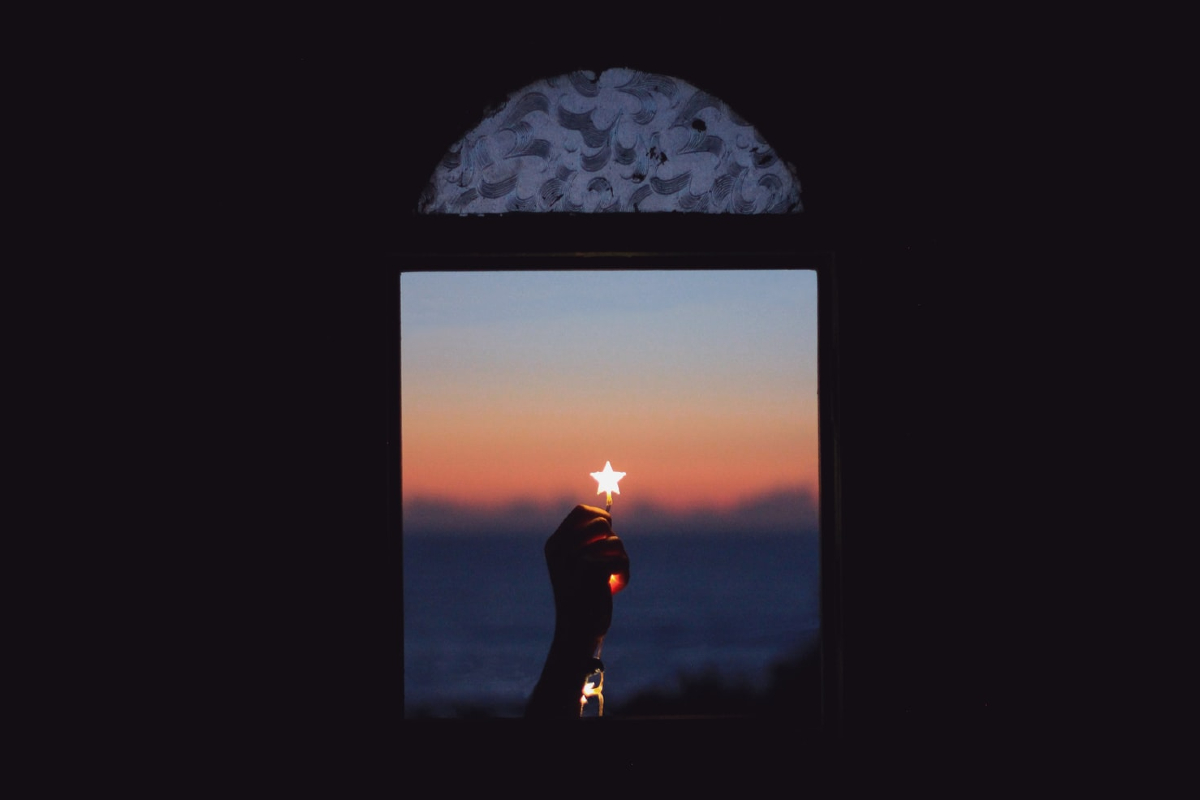 This image shows a window looking out to a blue to ornage sunset. A bright star shape sits at the centre of the photo.
