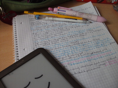 In this image, there is an electronic reading device in the bottom left of the image. Underneath the device is an A4 sized notepad that has some handwritten notes, by Rosa. On top of the notepad is a couple of pens.