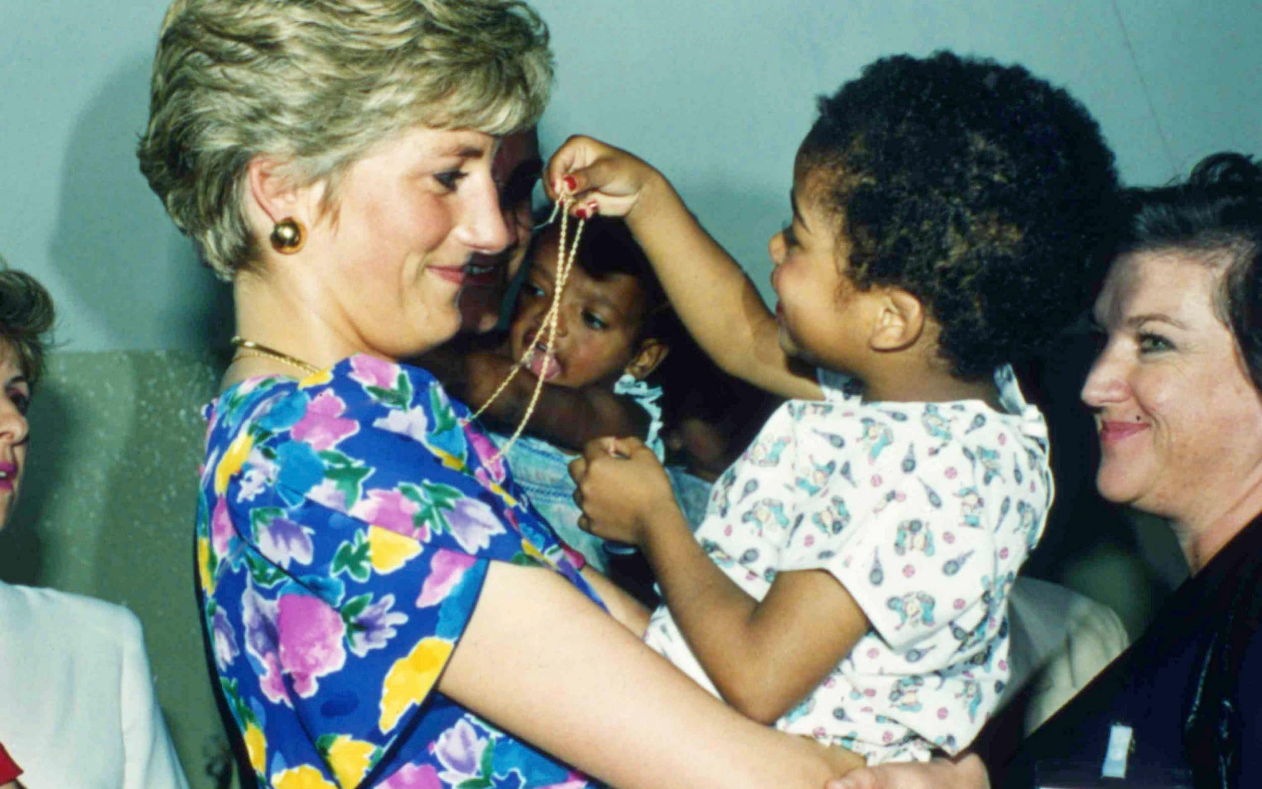 Princess Diana is pictured here holding a young child in her arms as the child plays with her necklace.