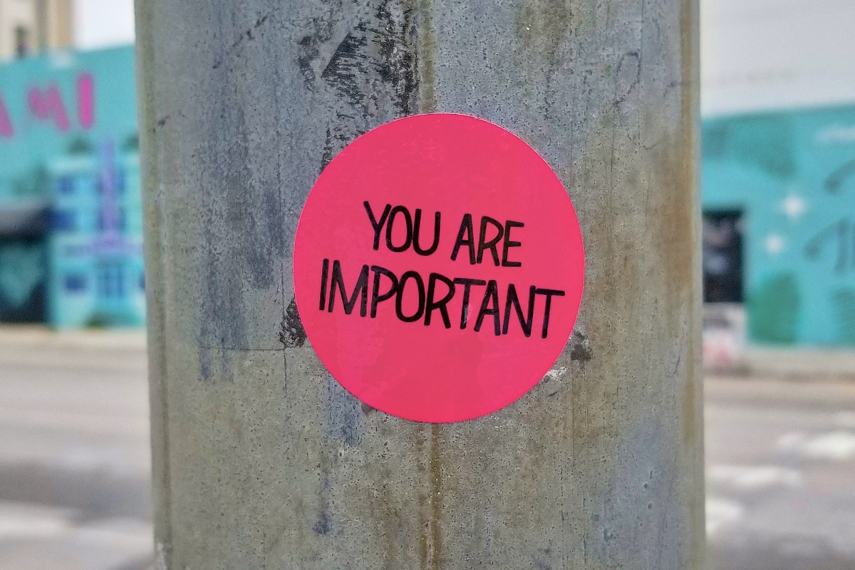 This image is of a wooden pole with a bright pink sticker on it reading 'you are important' in black font.