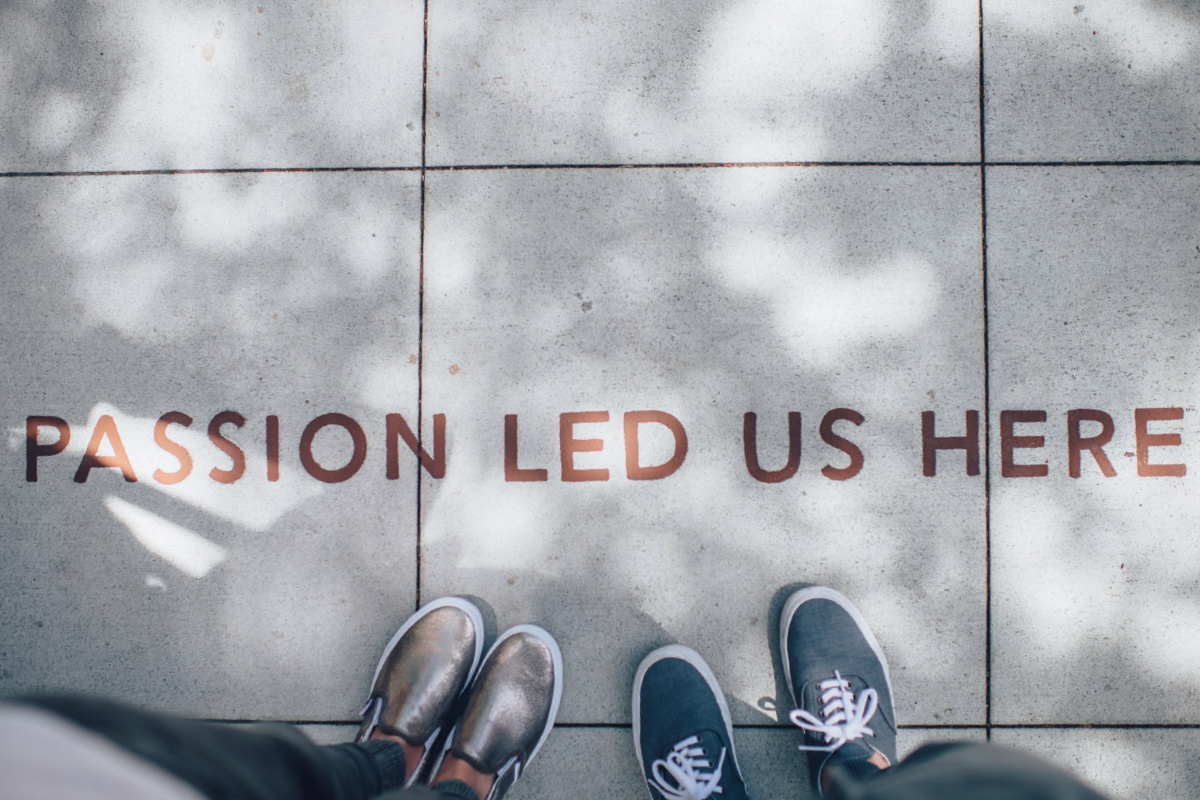 This image shows a photo taken facing towards the ground showing the feet of two individuals standing on concrete tiles. The floor has red bold capitalised font reading 'PASSION LED US HERE'