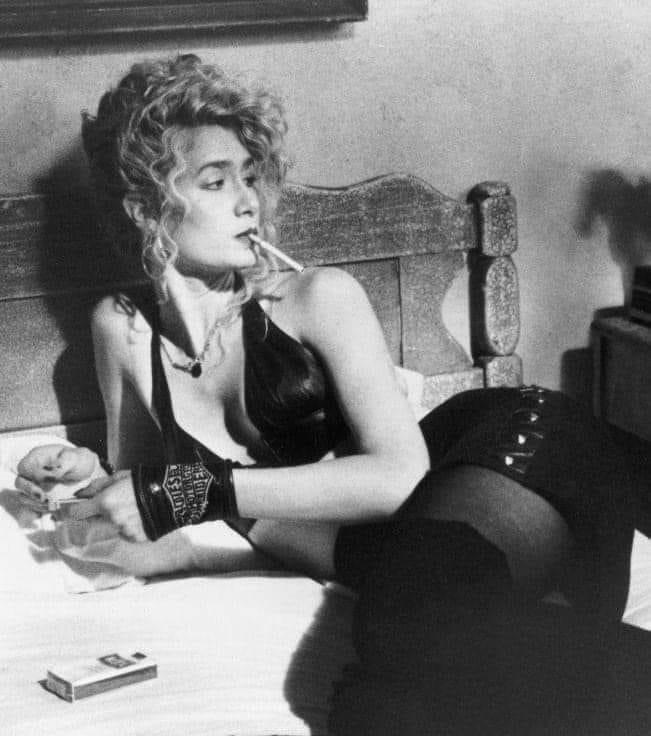 Laura Dern as Lula Fortune in Wild at Heart, David Lynch,1990. The picture is black and white and she is pictured looking away from the camera as she smokes a cigarette.