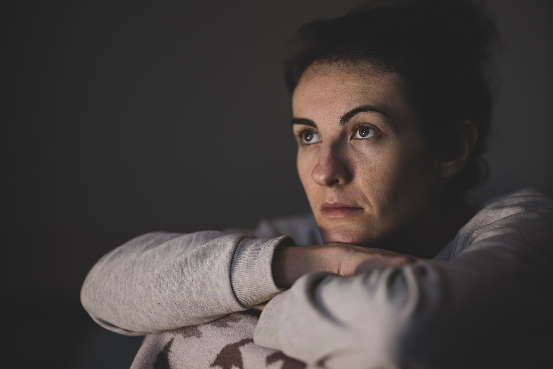 This image shows a woman looking miserable in dim lighting as she cannot get to sleep, she looks out to the distance.