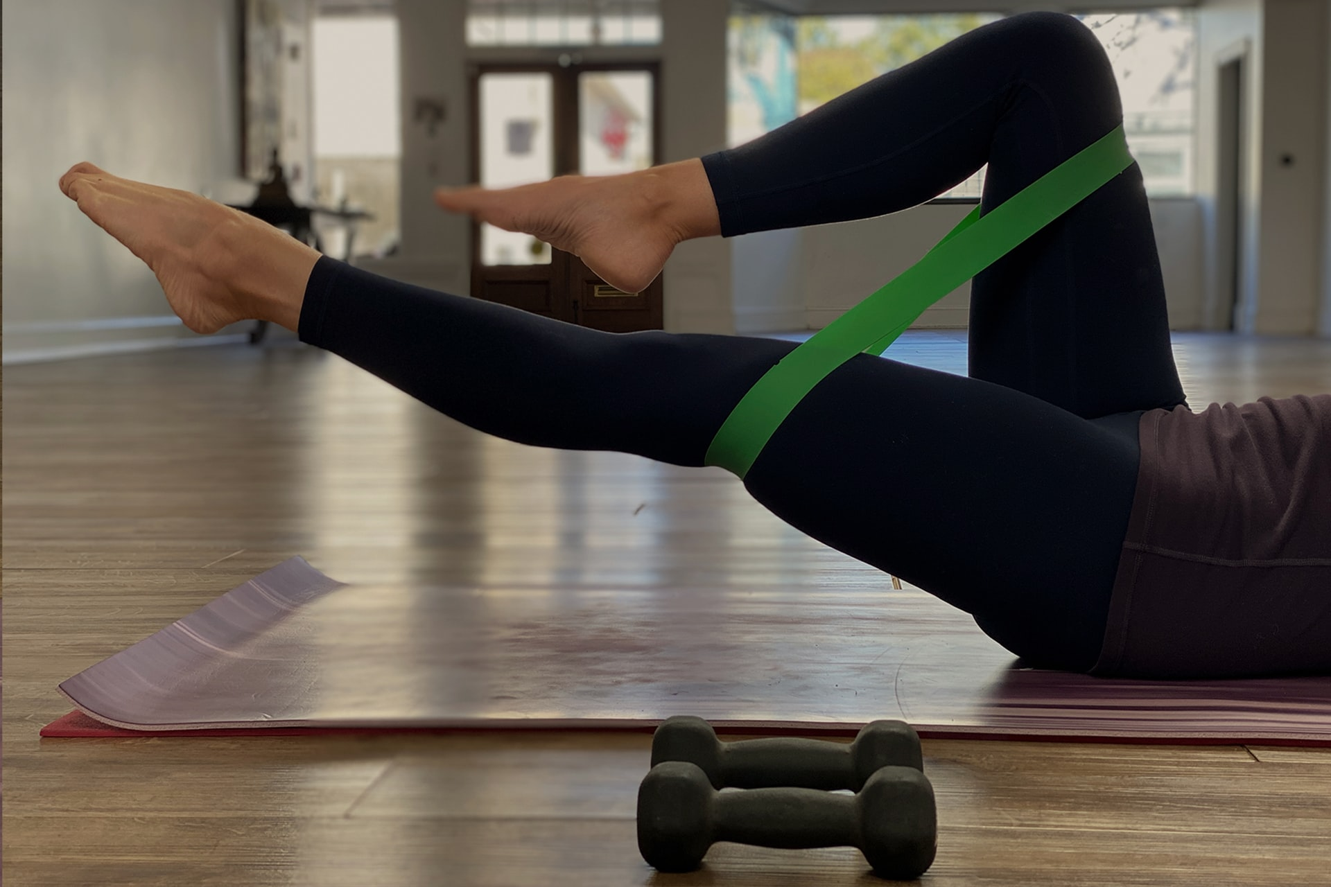 This image shows a women exercising on a yoga matt with resistance bands and dumbells.