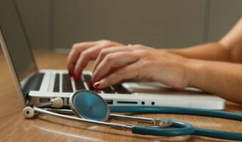 In this image, someone is typing on a laptop and a stethoscope is on the table next to the laptop.