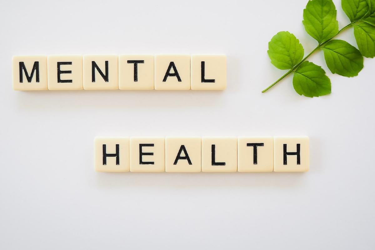 This image shows the words mental health spelled out with scrabble letters on a white background.