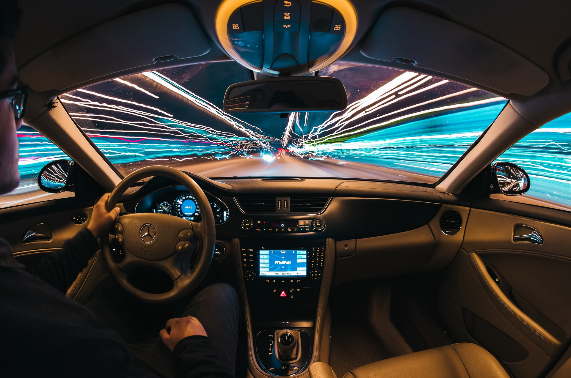 This image is taken from inside a sports car as a lens pictures the lights going past the vehicle.