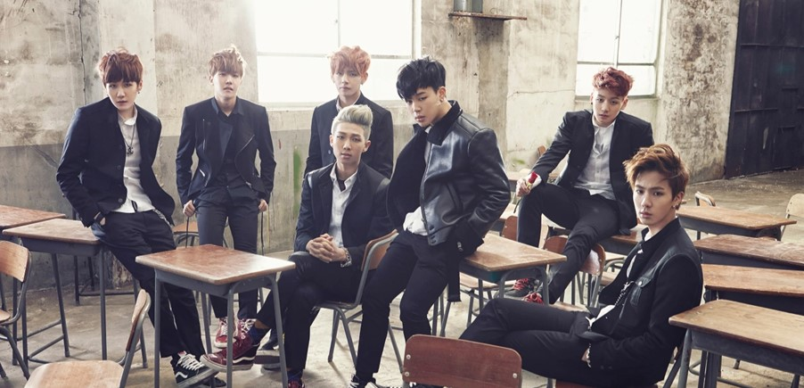 In this image, the boyband, BTS, are posing for a photo together. They are wearing black and white outfits, ruffled to look like rebel students.