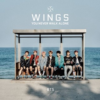 In this image, BTS are sat at a bus stop that is in front of the sea. It is an album cover for their album, Wings.