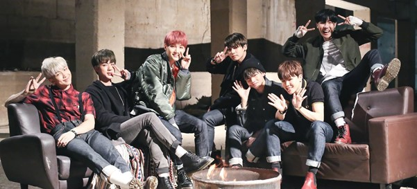 In this image, BTS are all wearing casual clothing and sat on a pair of sofas. They are posing for a camera, all smiling and pulling faces.