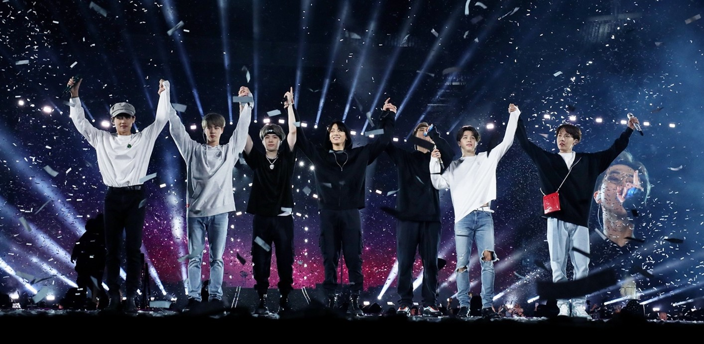 In this image, BTS have their arms connected together and raised in the air, like their about to take a bow. Confetti is falling around them as they're stood on a concert stage.