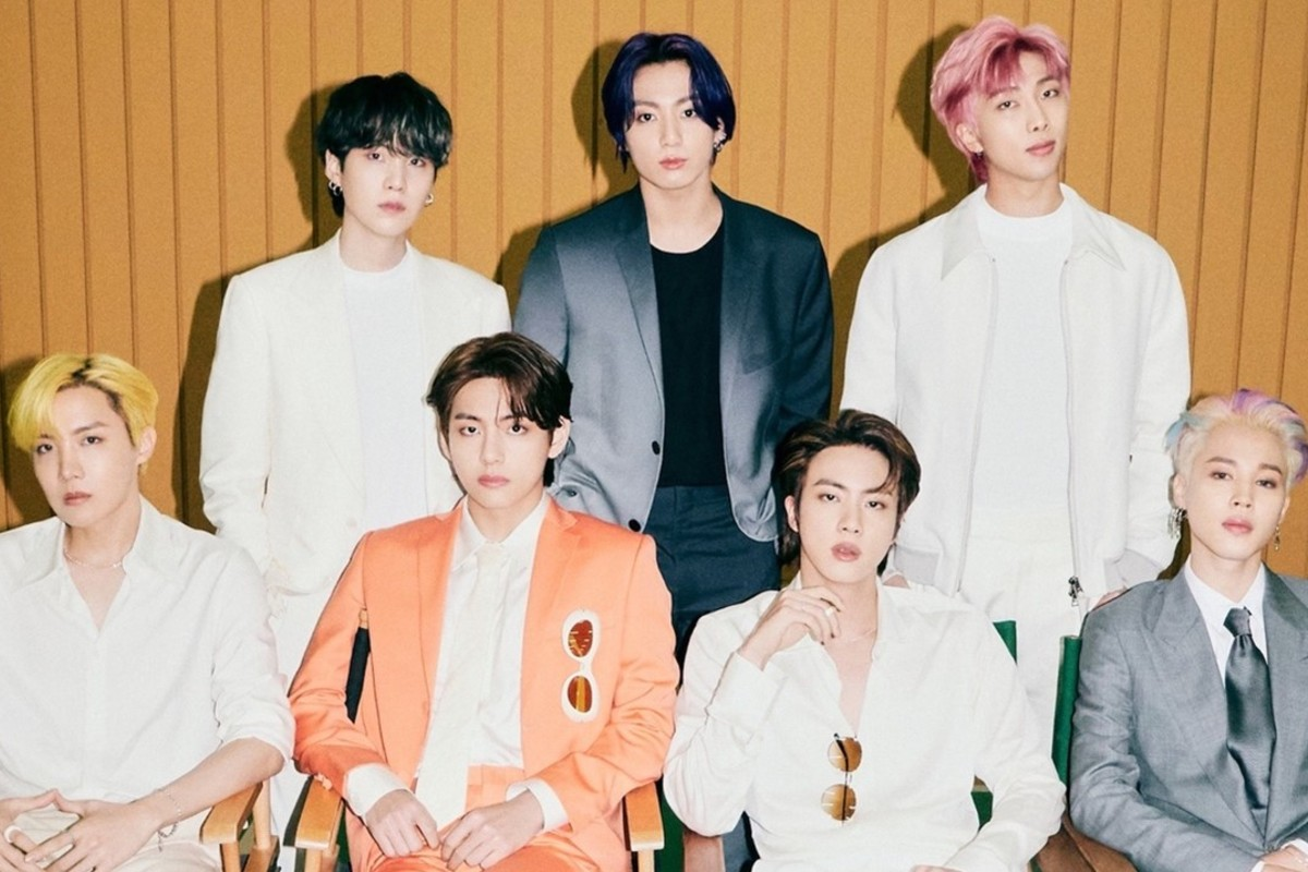 In this image, the boyband, BTS, are posing together for a photo. Four members are sat in chairs and the other three members are stood behind them.