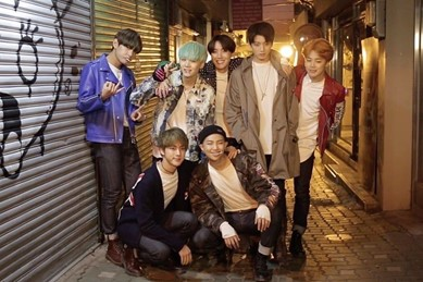 In this image, the boys are wearing casual clothing, like jeans, a white top and a light jacket. They are stood in an alleyway that has shutters decorated in graffiti on either side of them.