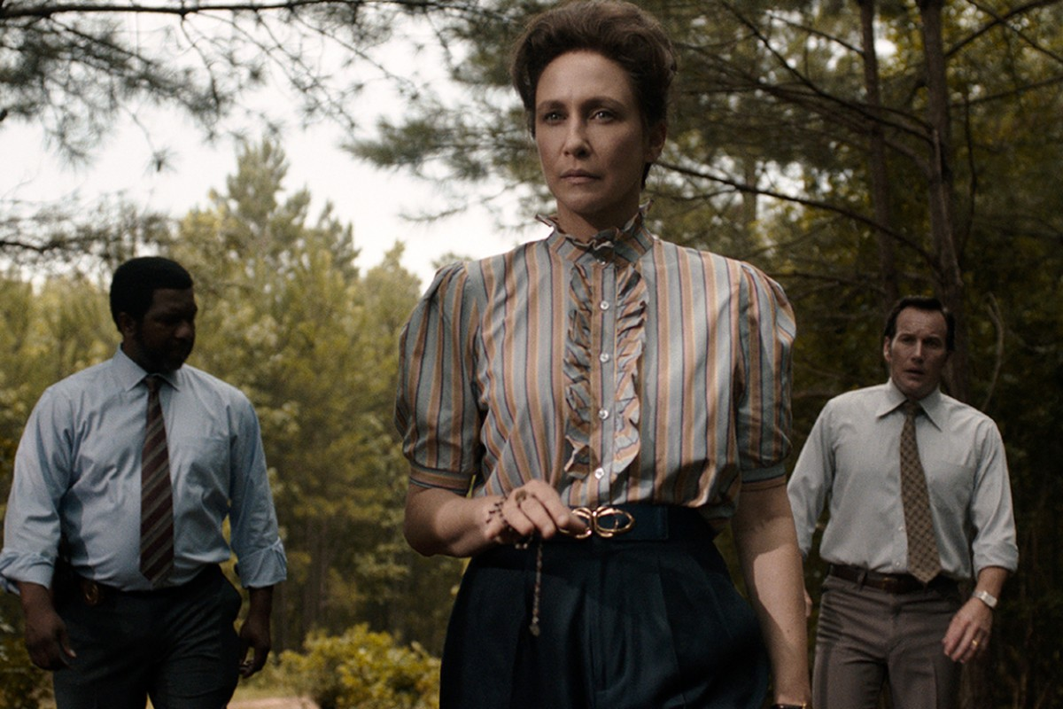 In this image, there is a police man in a shirt and suit to the left. In the middle is Lorraine Warren (character) holding a pendant in her hand. To the right is her husband, Ed Warren (character) also in a suit.