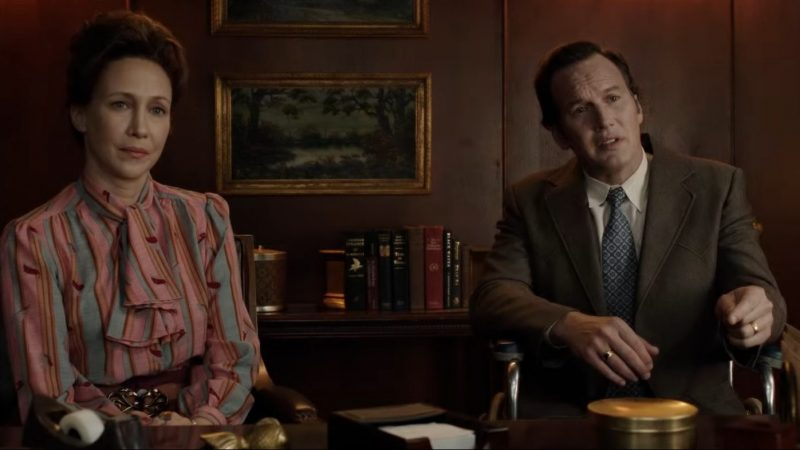 In this image, Ed and Lorraine Warren (the characters), are sat in an office wearing smart clothes. Both are sat in chairs next to each other.