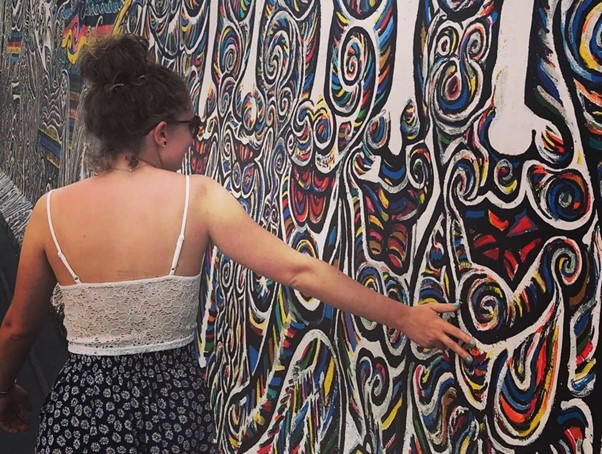 In this image, Emma is walking along and touching some wall art.