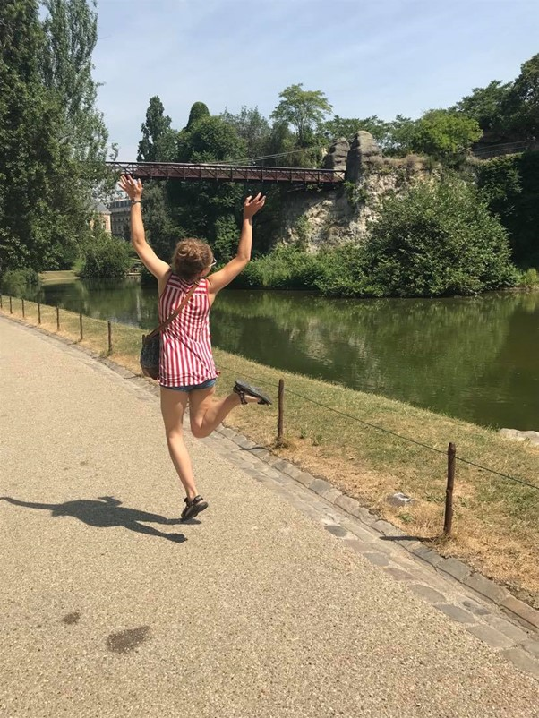In this picture, Emma is jumping with her arms in the air. She is jumping next to a river, that is surrounded by trees and there is a bridge in the distance.