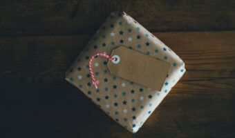 In this image, a present is wrapped in brown wrapping paper that is covered in stars.
