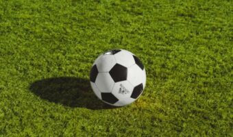 A black and white football is sitting still on a bright green football pitch.