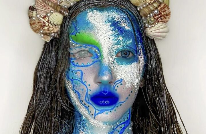 In this image, Niamh has painted her face blue, green and white to create a scaled water effect. She is wearing a band of giant beige shells on her head. Niamh has made herself look like a mermaid.