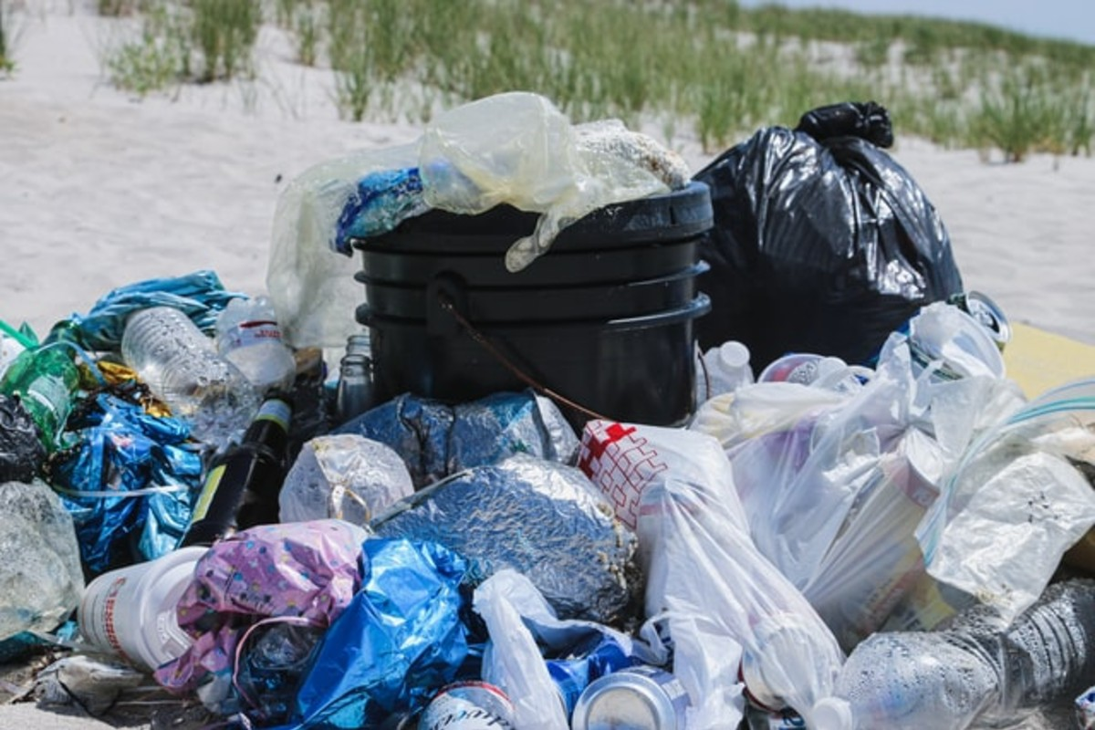 In this image, lots of filled plastic bags surrounding a bin on a beach.
