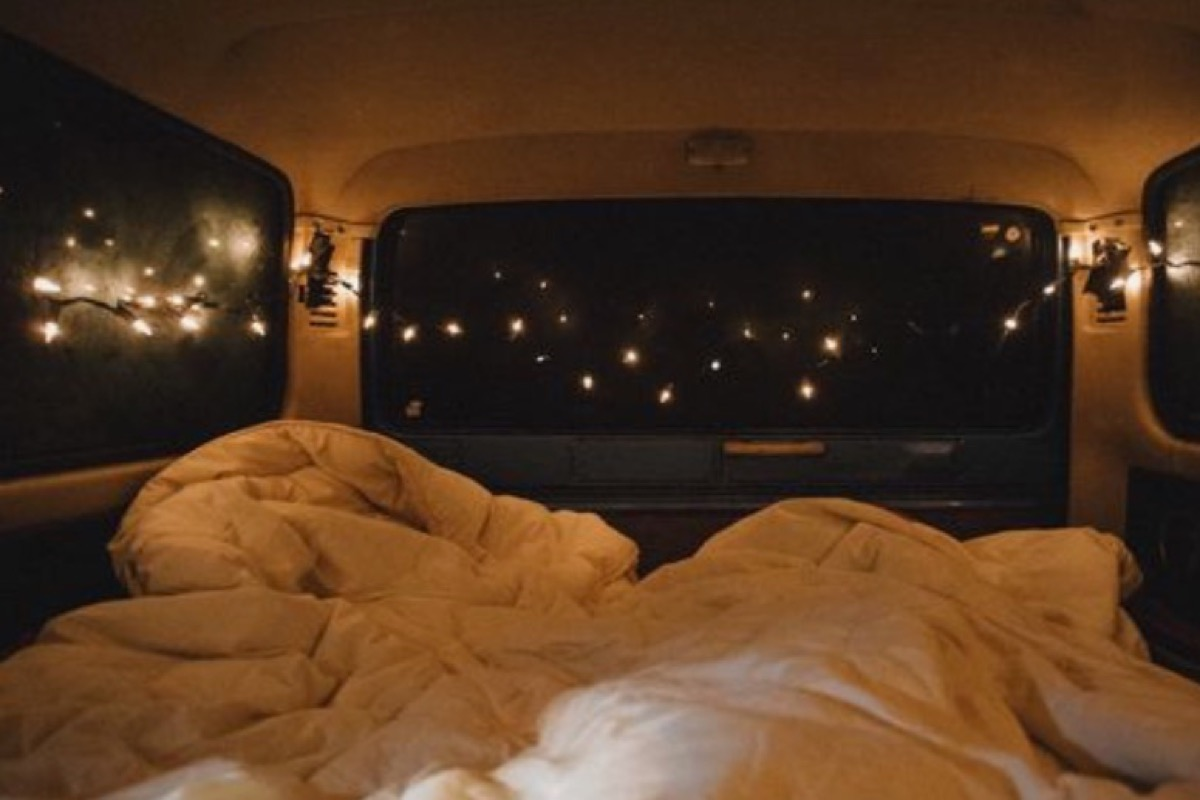 This image shows a cosy set-up in the back of a car. There are fairy lights around the top and a duvet in the bottom.
