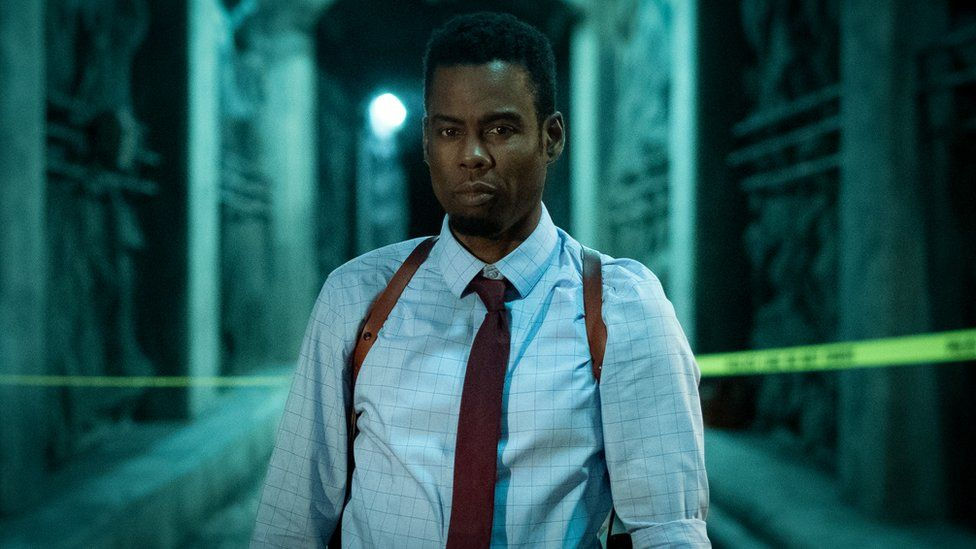 In this image, Chris Rock is wearing a white shirt with a red tie and stood in an industrial setting.