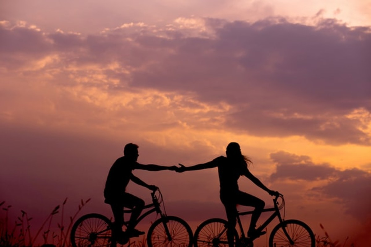 In this image, the silhouettes of a man and a woman on bikes whilst the sun is setting behind them.