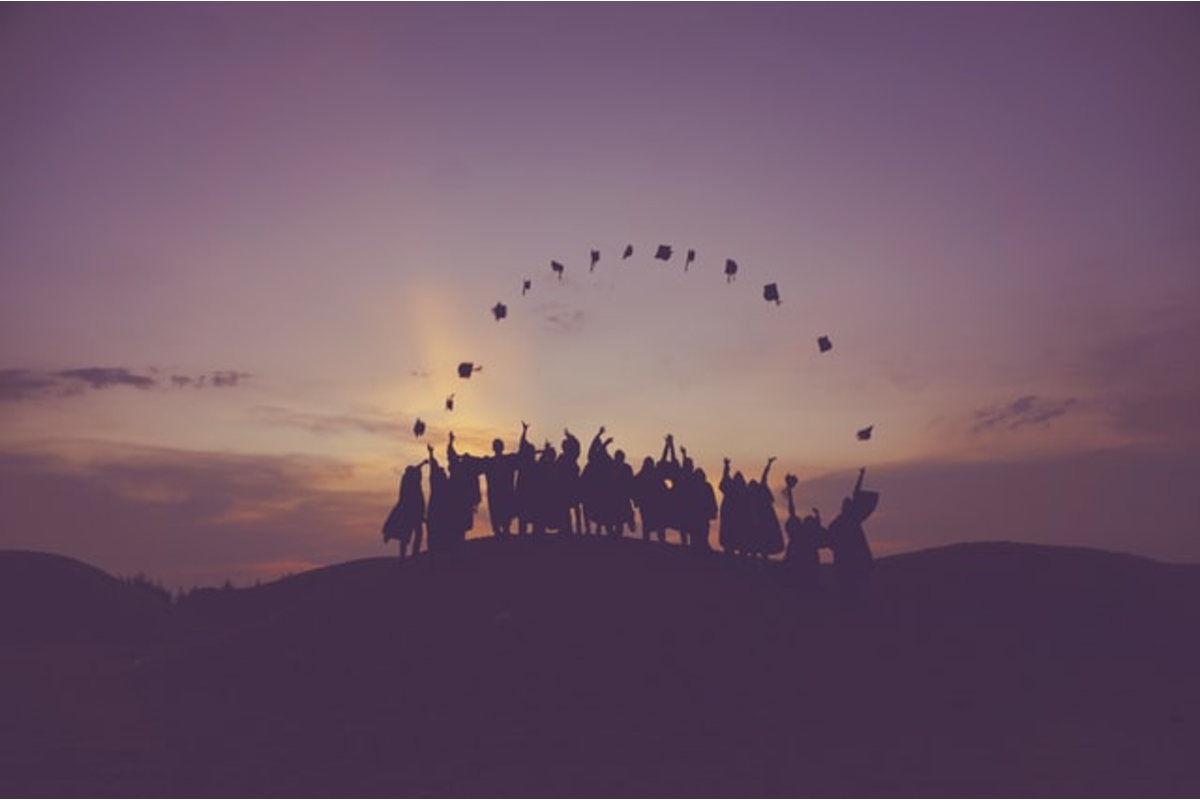 In this image, there is a group of graduates stood on top of a hill and they have thrown their graduation caps into the air.