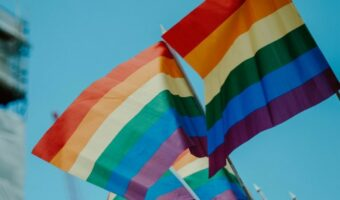 Against a bright blue sky, two pride flags are waving in the air.