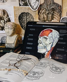 In this image, there are diagrams of organs on the wall, they look old. On a laptop screen is a diagram of inside the human head. Next to that laptop is an open textbook.