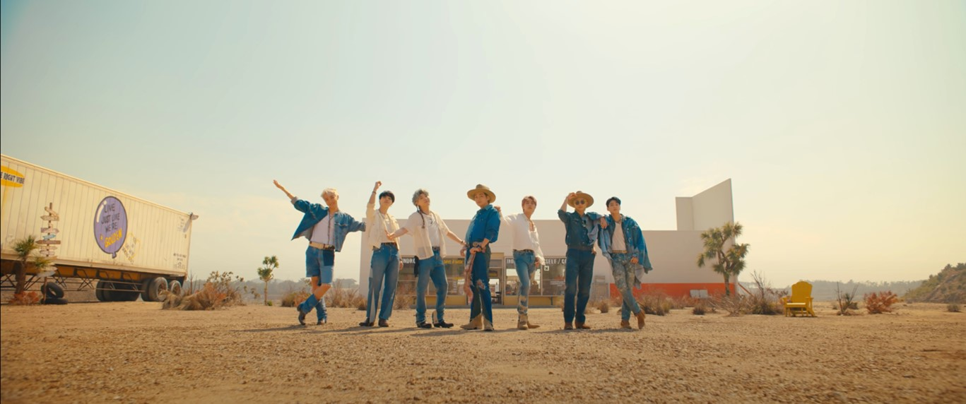 In this image, the boyband BTS are all stood in a horizontal line. They are wearing denim/western themed clothing. They are stood in a desert