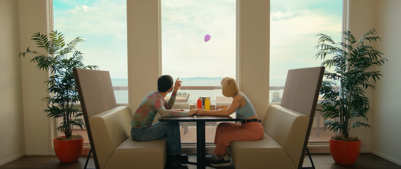 This is a screenshot from the BTS Permission to Dance music video. A couple are sat at a table, one on either side. They are looking out of a window as a single purple balloon flies past.