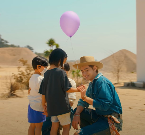 In this image, BTS band member, Tae/V, is crouched with two kids. One of the kids is holding a purple balloon.