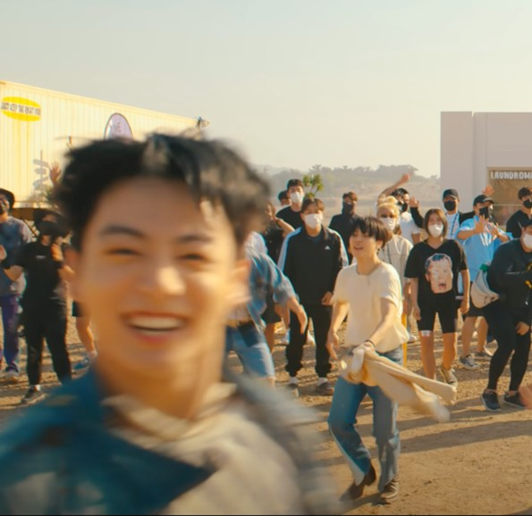 In this image, Jungkook, a member of BTS, is jumping in front of the camera. However, the screenshot has been taken mid-jump.