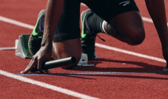 In this image, an athlete is crouched and ready to run.