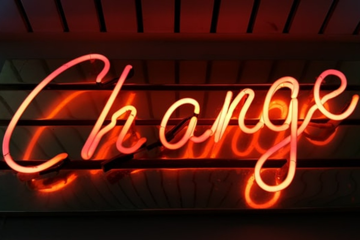 In this image, the word 'Change' has been made out of LED lights and they are glowing red on a wooden wall.