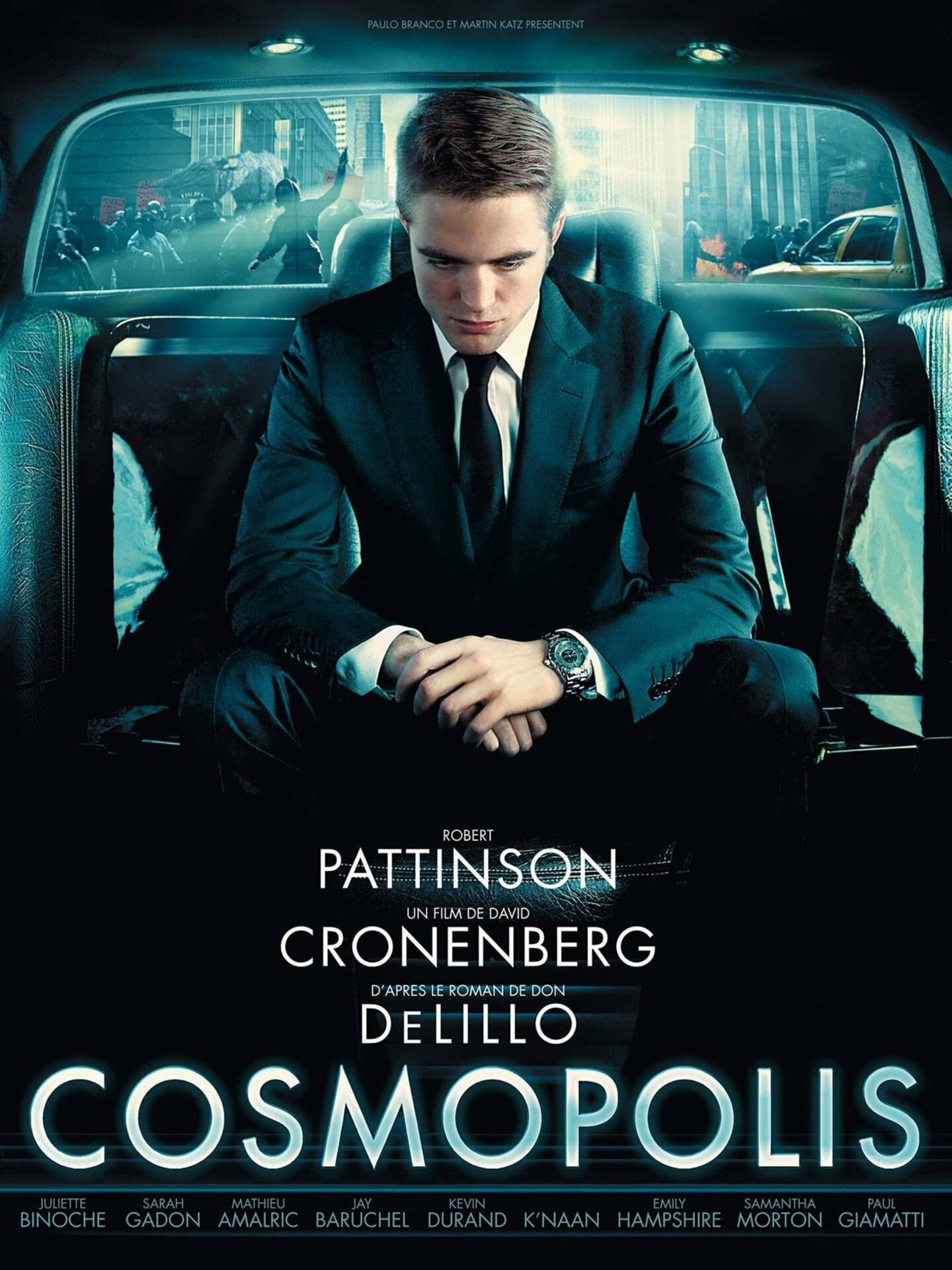 This is an image of the Cosmopolis movie poster. Actor Robert Pattinson is wearing a black suit and sitting in the back of a car.