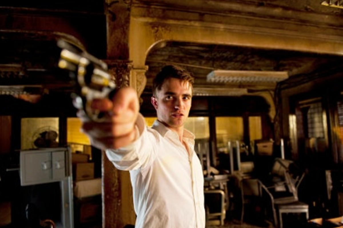 In this image, actor Robert Pattinson is holding a revolver at a character behind the camera. His is in a wooden building and is wearing a white shirt.