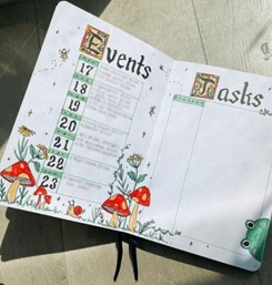 This is an image from AmandaRachLee's Instagram page. It shows a bullet journal that Amanda has created, an events list and a task list. At the bottom of the page are some hand drawn red and white mushrooms.