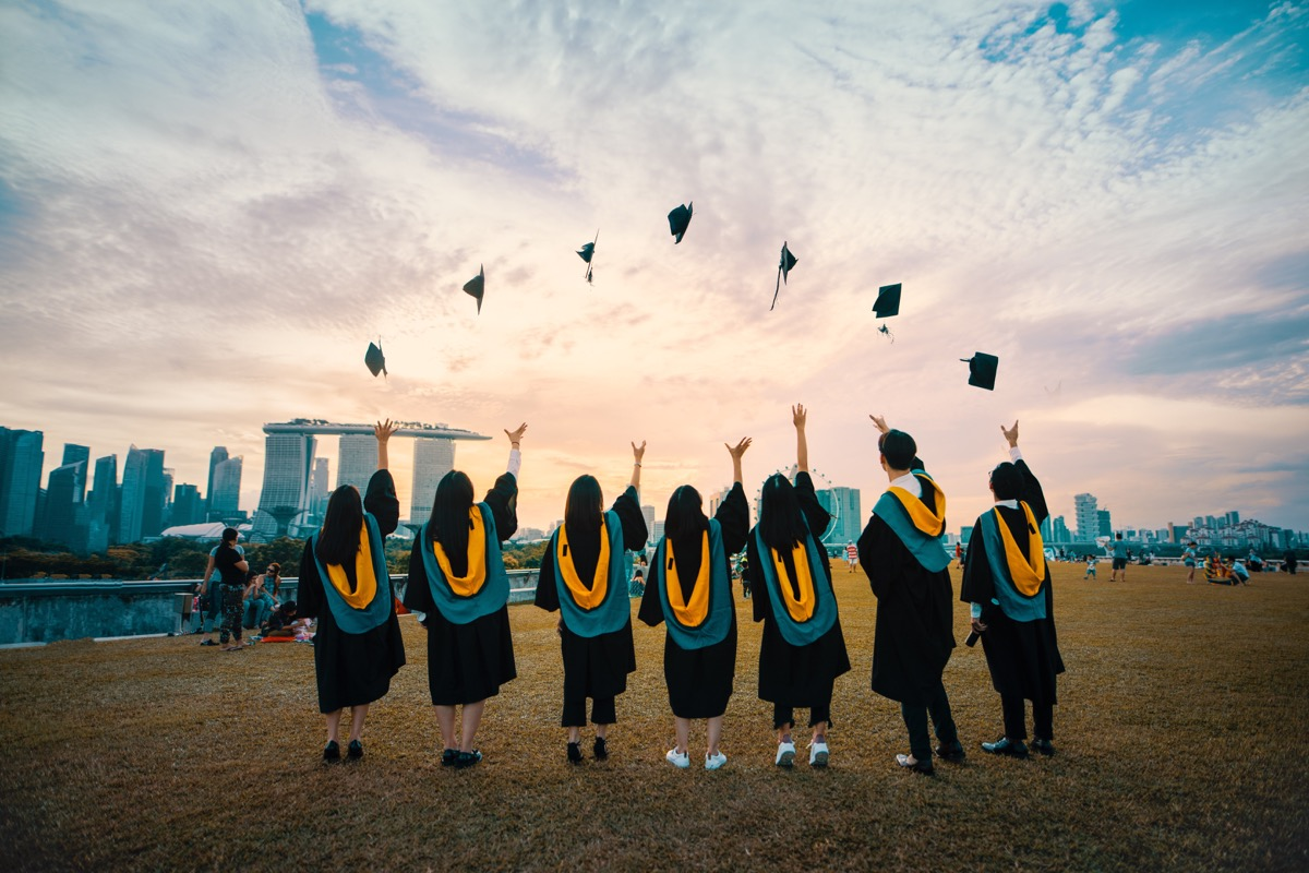 This image shows a line of people that are wearing graduation gowns and throwing graduation caps into the air.
