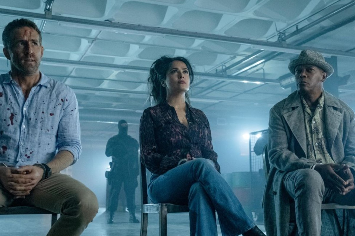 In this image, Ryan Reynolds, Salma Hayek and Samuel L. Jackson are sat on chairs in a row.