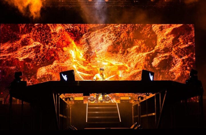 In this image, musician Illenium is performing behind his DJ desks on a stage. The stage wall behind him has an image of bright orange rocks and fire.