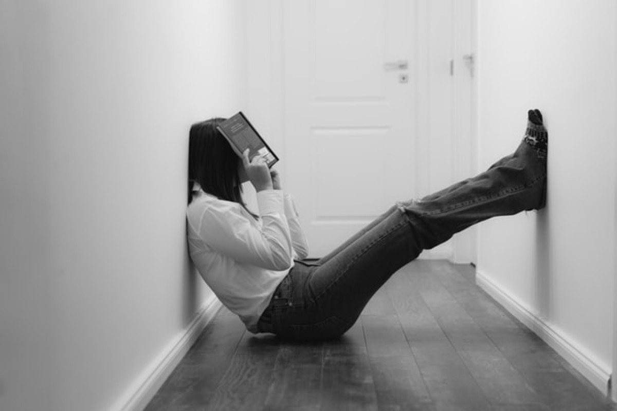 In this image, someone is sat in a narrow hallway and has their feet resting on the opposite wall. They are also holding a book over their face. The image is black and white.