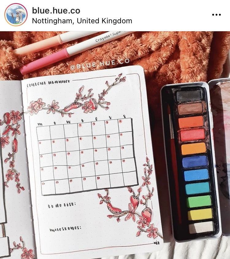 This image is from Rachel's Instagram. The image is a hand drawn calendar that she has drawn in her bullet journal. The page is decorated with blossom branches. Next to her journal is a paint set.