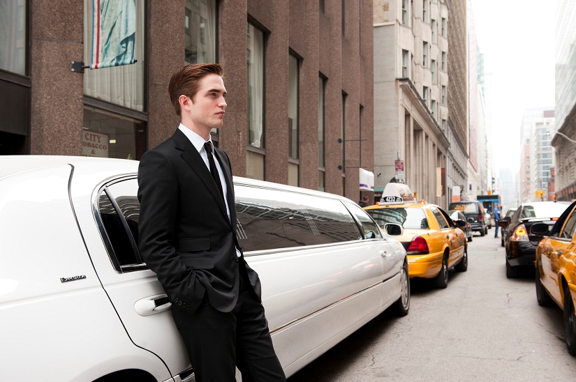Robert Pattinson is leaning against a white car whilst wearing a black suit. It looks as though he is stood in the middle of a New York street.