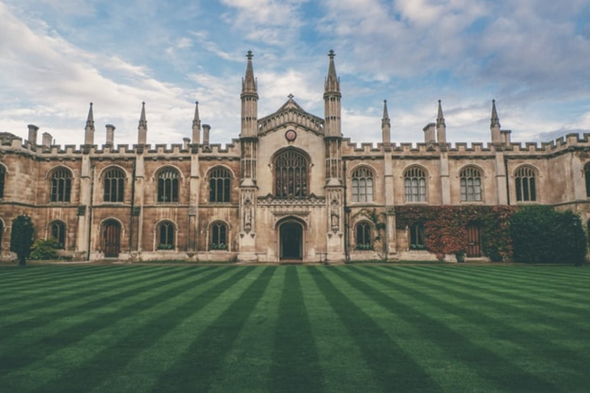 In this image, a historical building, perhaps used as a university, is stood at the end of a mowed lawn.
