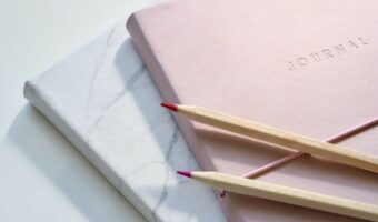 In this image, two journals are piled on top of each other. the one on the bottom has a white and black marble pattern. The one on top is a baby pink colour and has 'journal' imprinted on the front. On top of the pink journal are two colouring pencils.